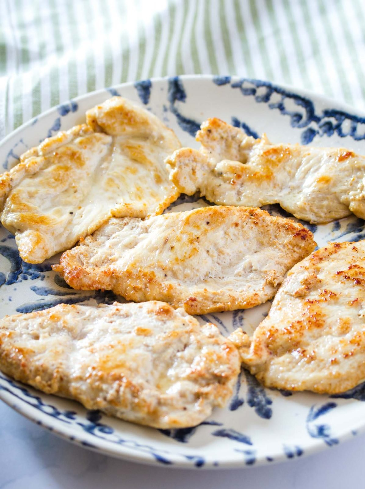 chicken breasts that have been lightly browned and cooked through on a blue and white dinner plate