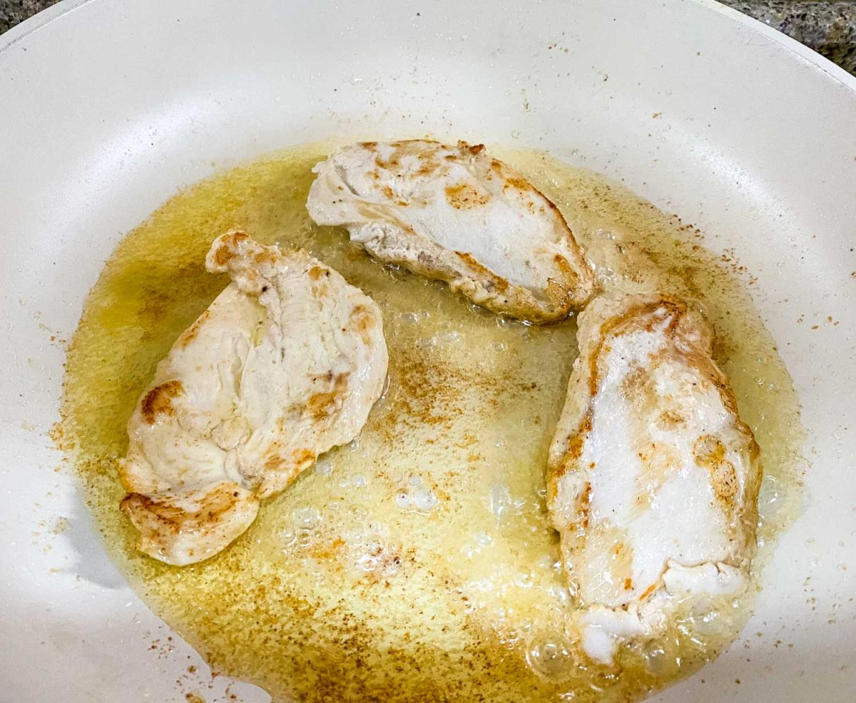 boneless skinless chicken breasts grilling in a pan with butter