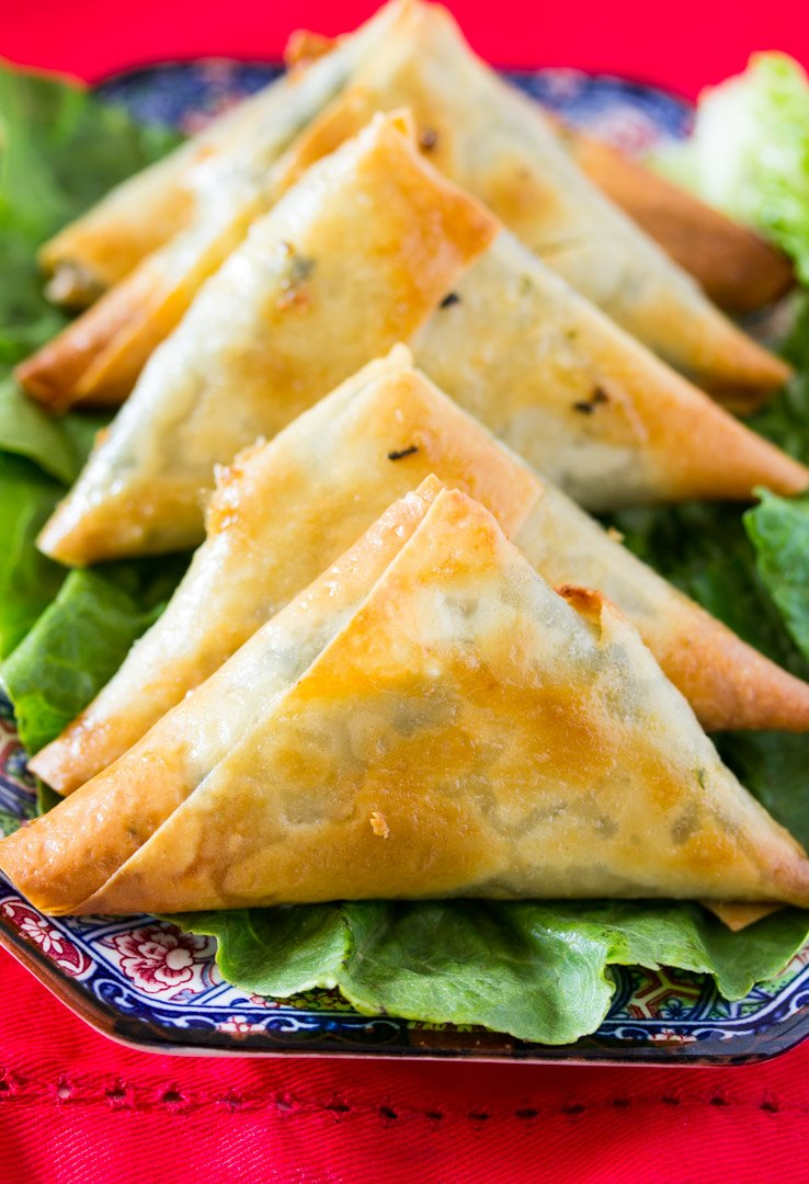 Baked Spinach & Feta Cheese Samosa on a bed of green lettuce on a beautiful blue plate