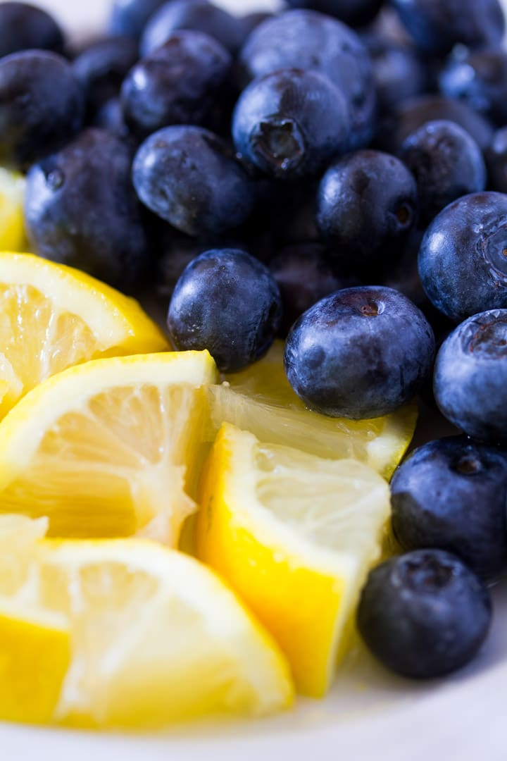 Blueberries and lemon slices on a white plate