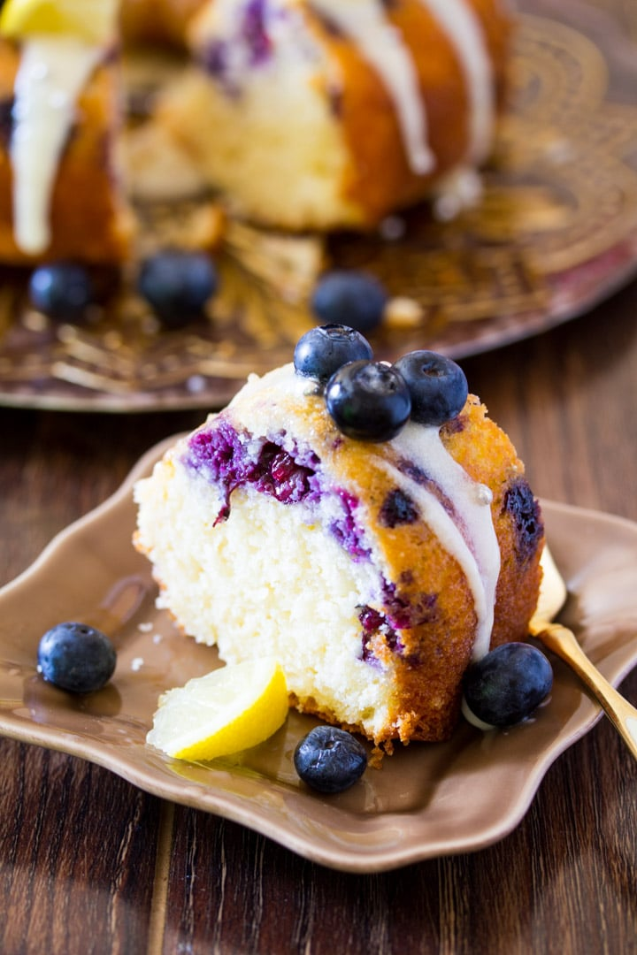 A slice of blueberry lemon cake drizzled with cream cheese icing