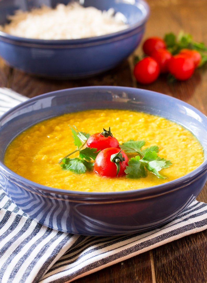 pakistani daal pictured in a blue bowl, garnished with cherry tomatoes and fresh coriander