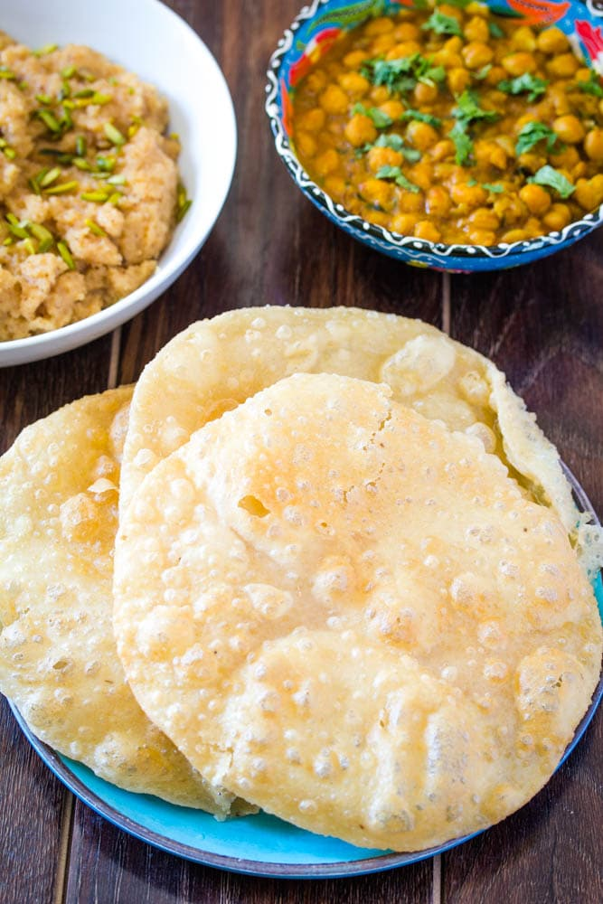 Poori on a blue plate served with chana masala and suji ka halwa