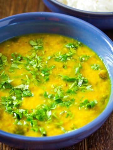 Moong Dal Tadka served in a blue bowl, garnished with chopped coriander. Served with white rice.