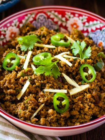 Pakistania keema served in a red bowl with rice and salad