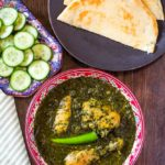Palak Chicken served in a red bowl, along with cucumbers and pita bread
