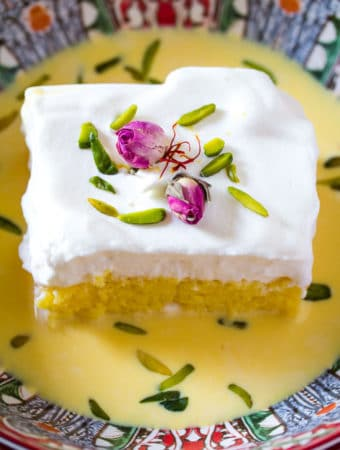 Saffron Milk Cake in a red bowl with rose buds and slivered pistachios