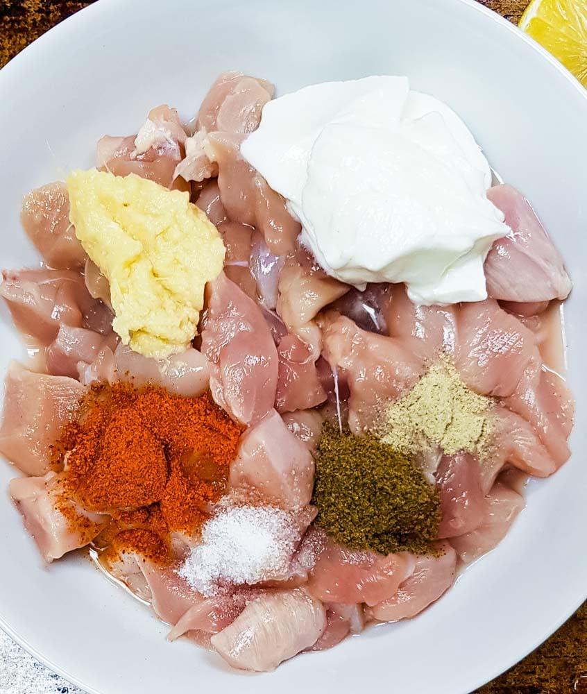 Ingredients for chicken tikka masala marinade: boneless chicken breasts, yogurt, ginger garlic paste, spices and lemon juice.