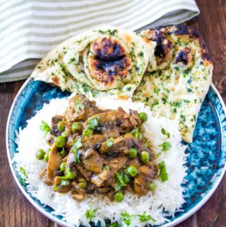 Mushroom Masala served on a bed of white rice with a side of garlic naan.