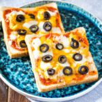 bread pizza with olives and cheese on a blue plate
