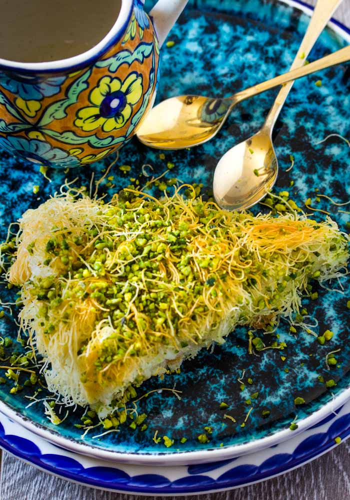 Slice of Kunafa on a turquoise plate next to two gold spoons.