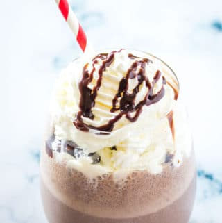Chocolate banana milkshake in a round glass topped with whipped cream and syrup.