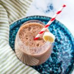 Coffee Banana Smoothie in a round glass with a red and white striped straw.