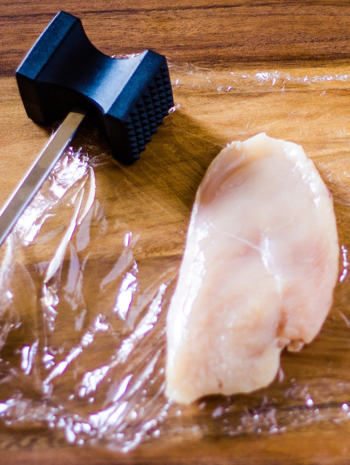 A chicken breast and a kitchen mallet on a wooden cutting board.