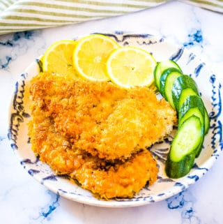 Breaded chicken cutlets on a blue and white plate with lemon slices and sliced cucumber.