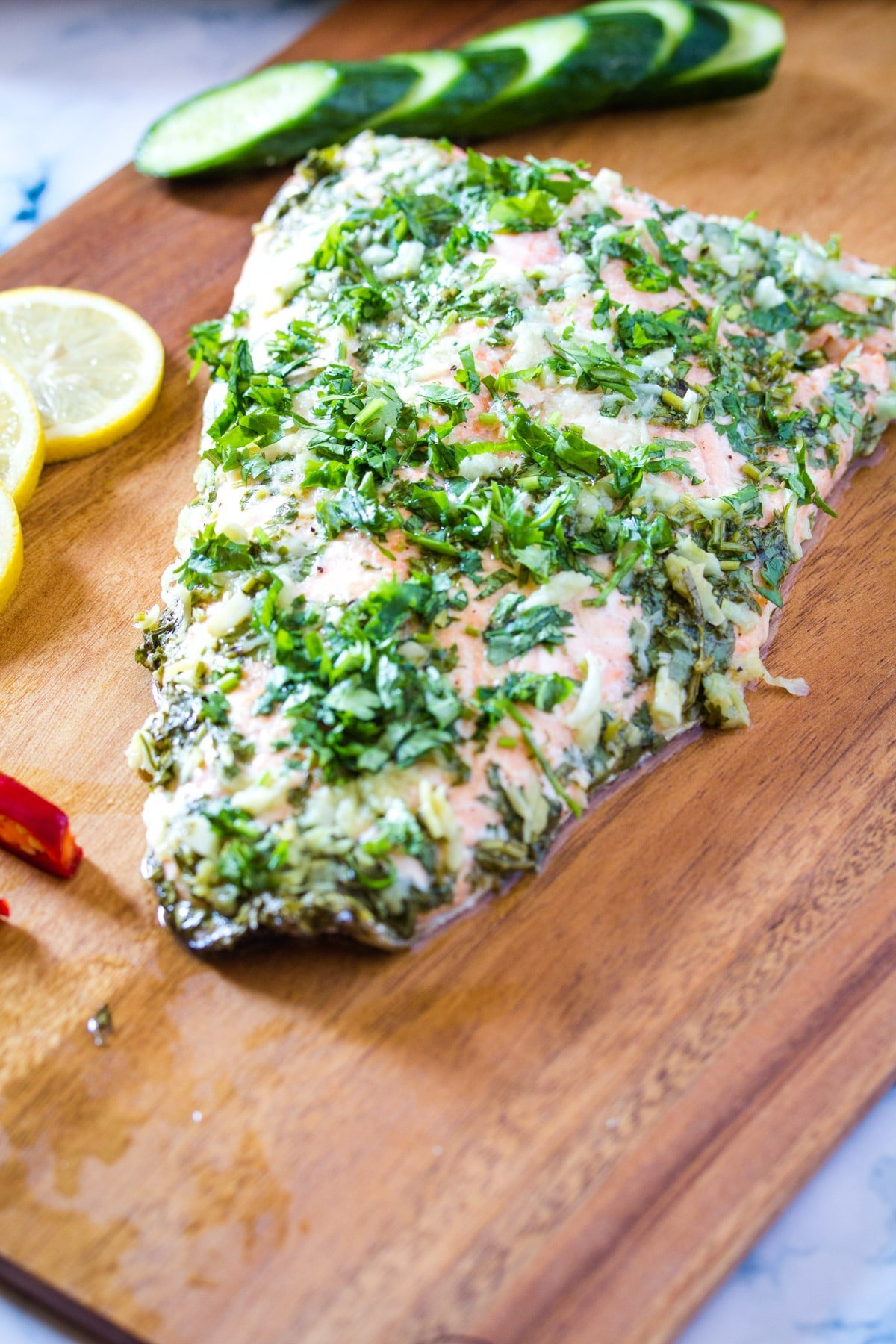 baked salmon served on a wooden cutting board garnished with chopped coriander.