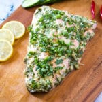 lemon garlic butter salmon on a wooden board garnished with coriander.
