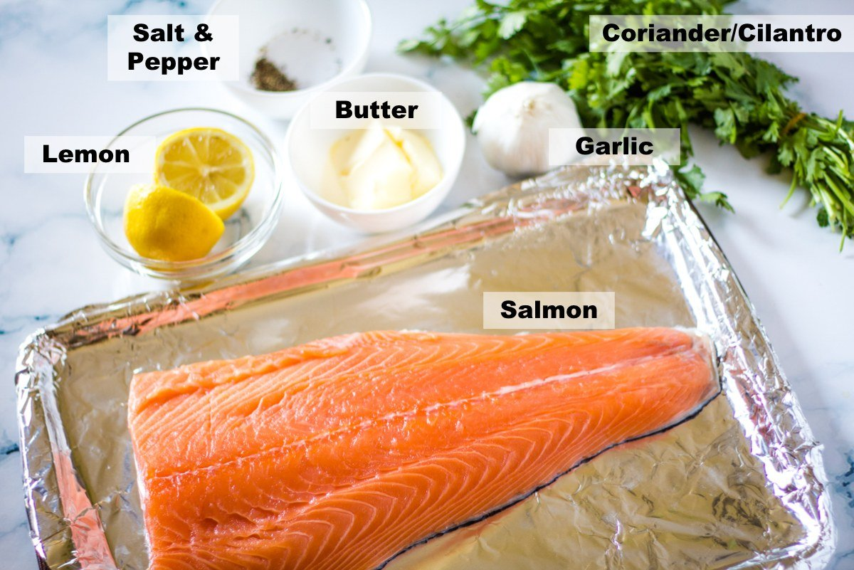Ingredients for baked salmon laid out on a white marble backdrop.