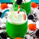 Green polyjuice potion in a glass with spooky decorations.