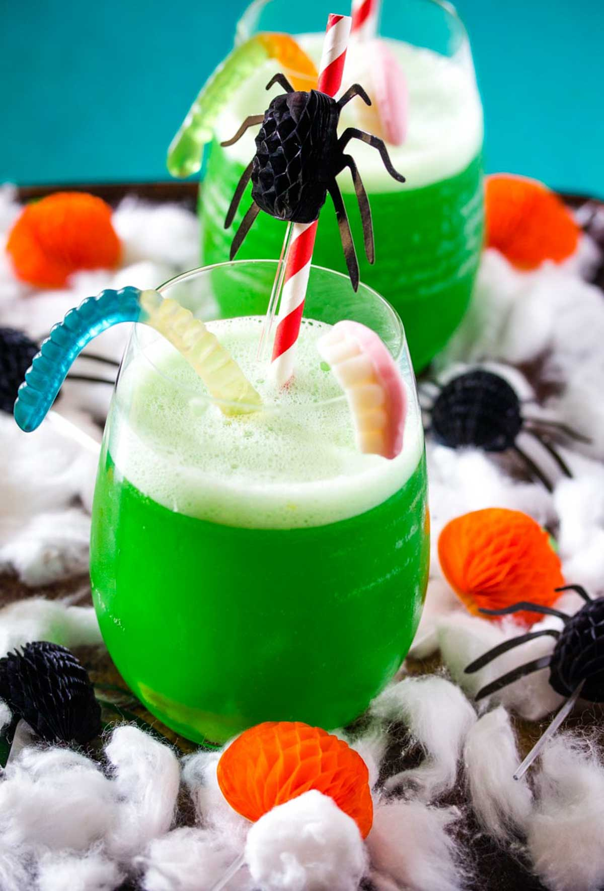 Polyjuice Potion in a round glass decorated with gummy worms and Halloween decorations.