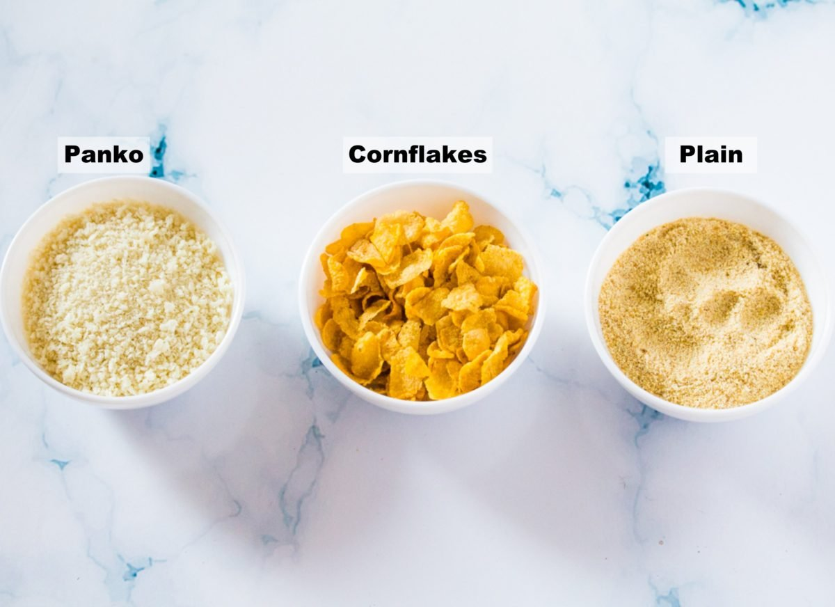 Panko, cornflakes, and plain bread crumbs in three white bowls, displayed on a white marble backdrop.