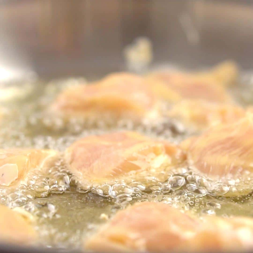 battered chicken frying in oil before being flipped