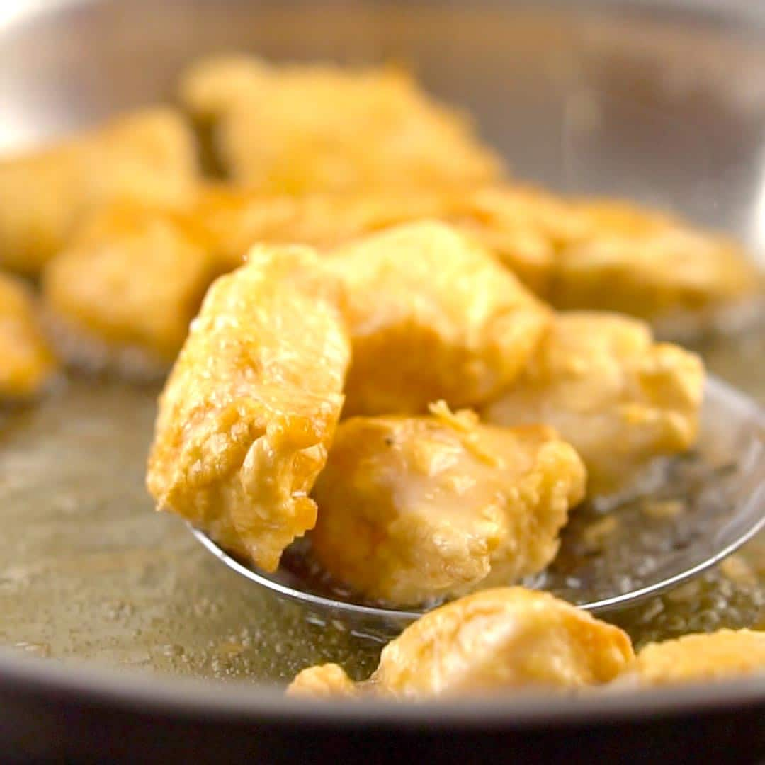 golden pieces of fried chicken being removed from wok with a slotted spoon