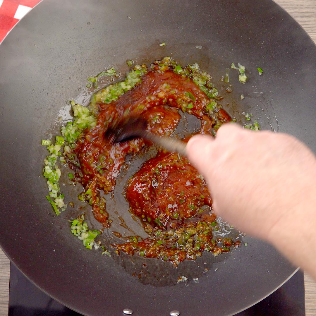 hand stirring ketchup, salt and soy into green onion mixture