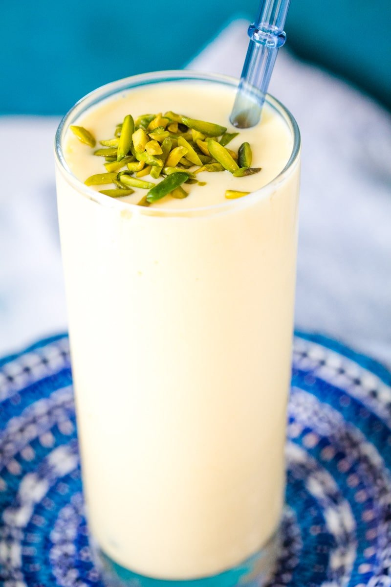 Mango Lassi in a tall glass with a blue straw.