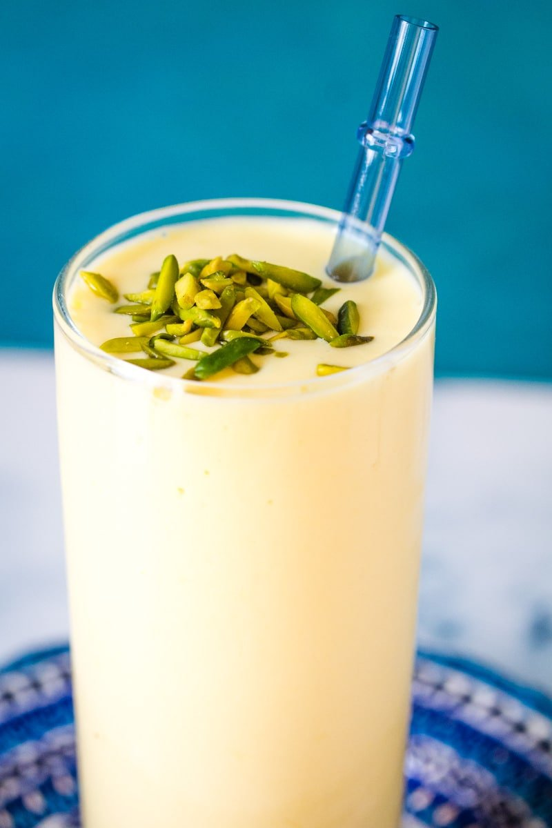 close up of mango lassi garnished with slivered pistachios