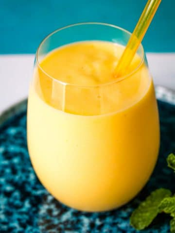 Mango milkshake with a yellow straw inserted.