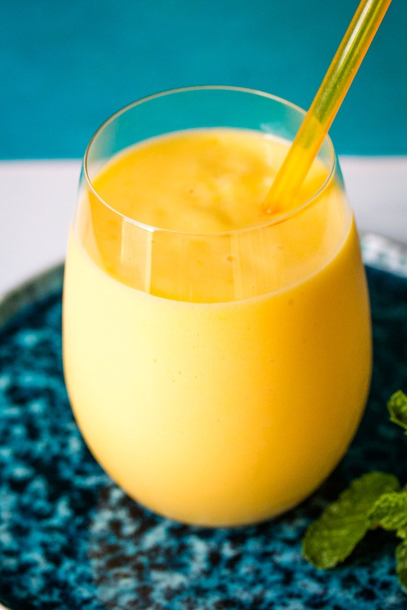 Bright yellow mango milkshake in a clear glass on a blue plate.
