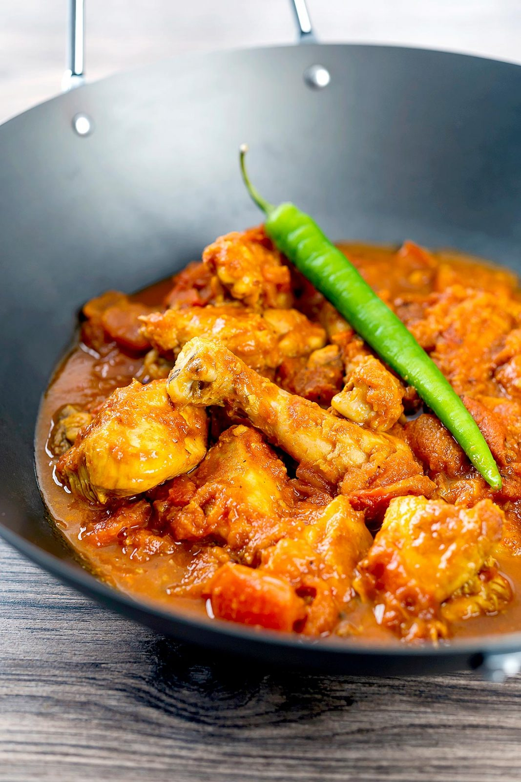 Tomato chicken karahi in a black wok topped with a single green chillie.