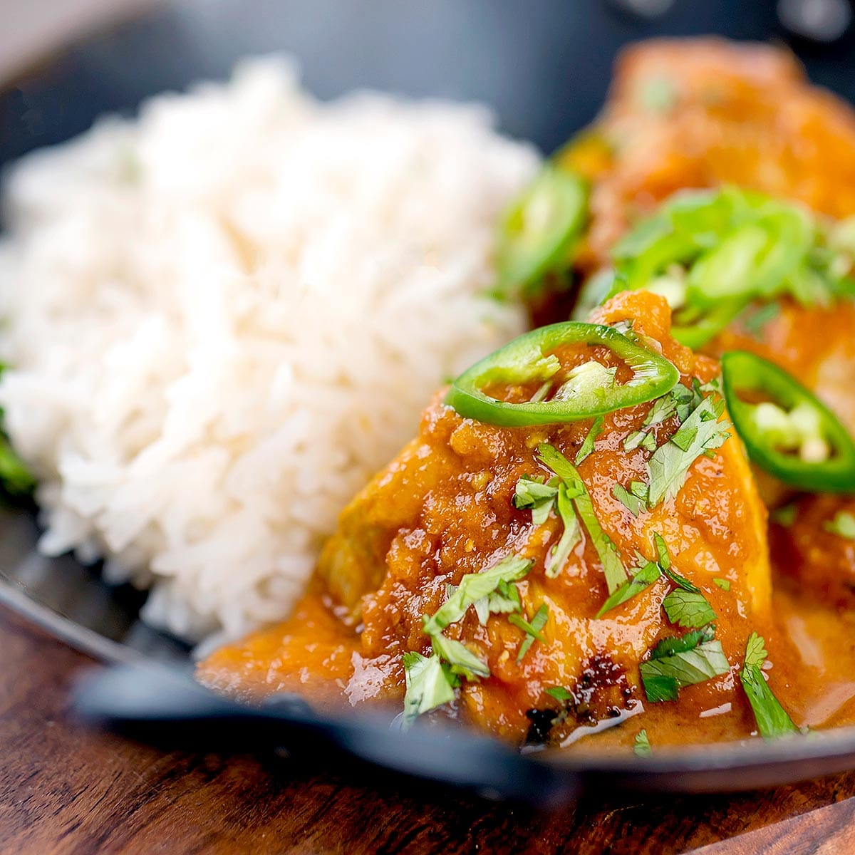 Close up shot of chicken karahi with white rice in a black wok.