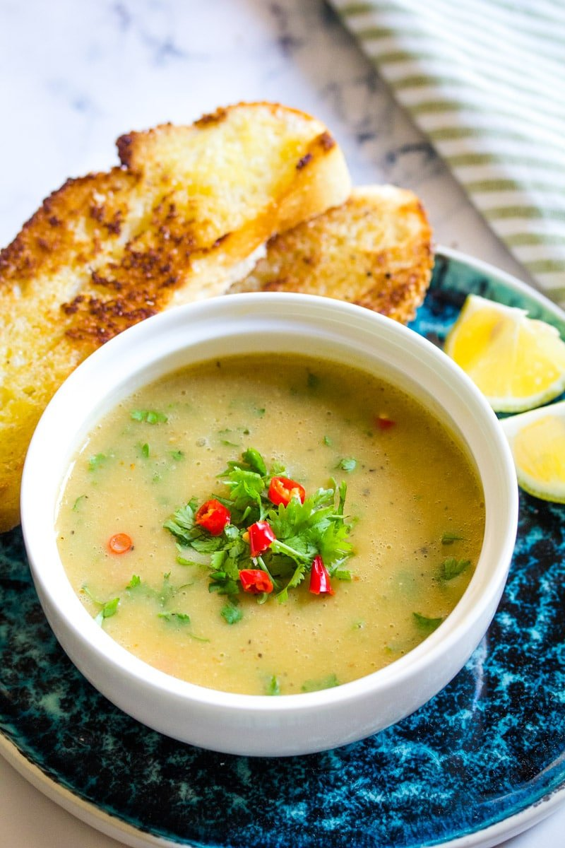 red lentil soup in a white bowl topeed with red chillies and coriander.
