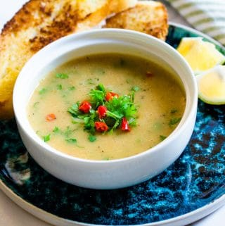 yellow lentil soup in white bowl placed on a blue plate.