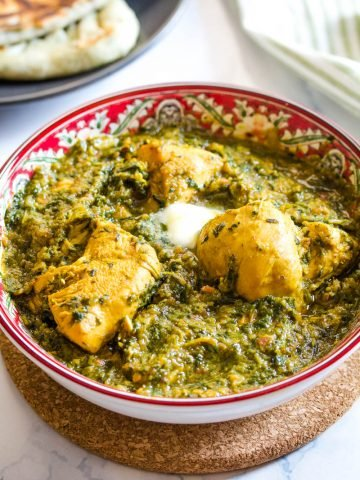palak chicken topped with butter, and served in a red bowl.