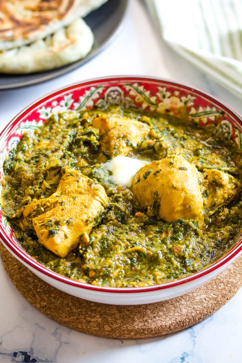 Pakistani chicken palak in a red bowl placed on top of brown table pad.