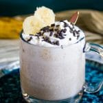 banana milkshake in a glass bug topped with whipped cream, sprinkles and banana slices.