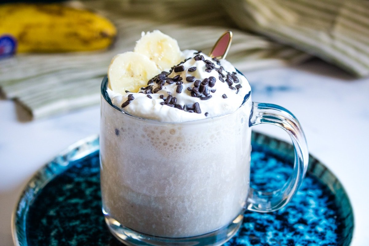 shake made with bananas and milk in a glass mug, on a blue plate.