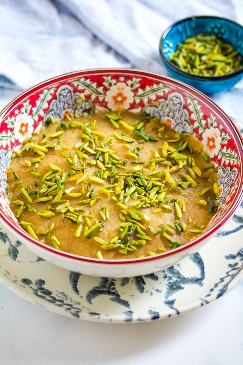 Close up shot of basan halwa served in a red bowl and topped with green pistachio nuts.