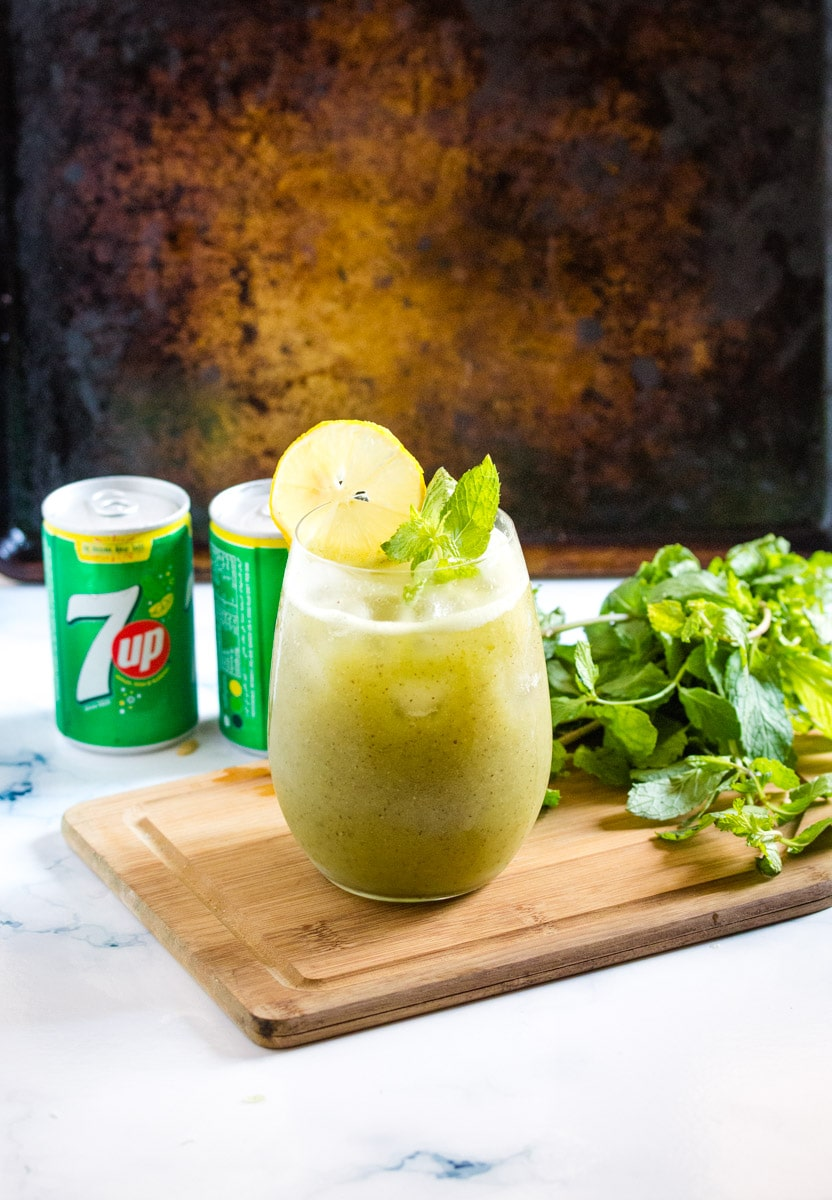 juice made with kiwi and 7up in a glass placed on a wooden serving board.