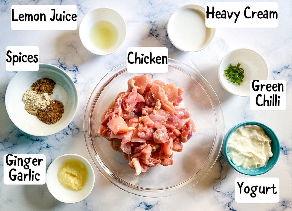 photo of ingredients needed to make murgh tikka on a white marble backdrop.