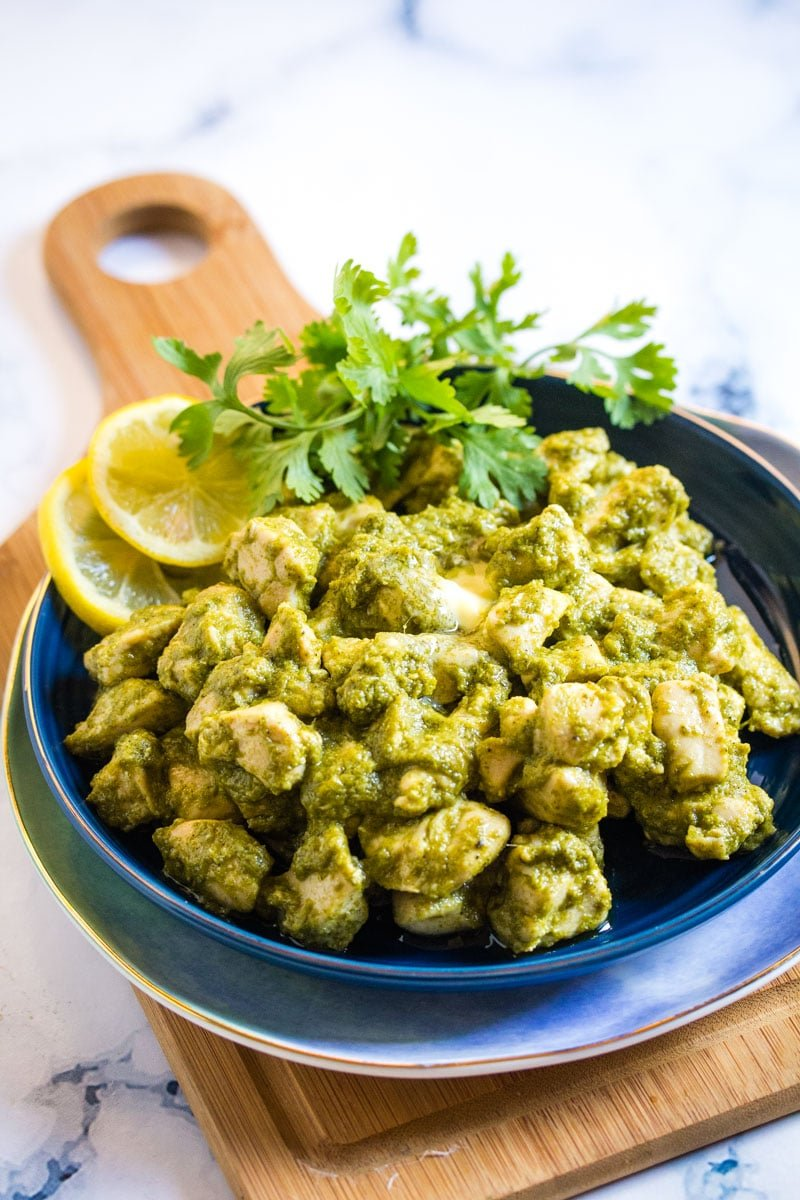 Green chicken handi served on a dark blue plate, placed on a small serving wooden board.