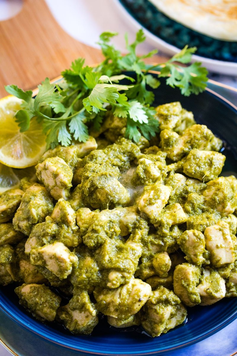Close up shot of hara masala chicken garnished with fresh coriander leaves and lemon slices.