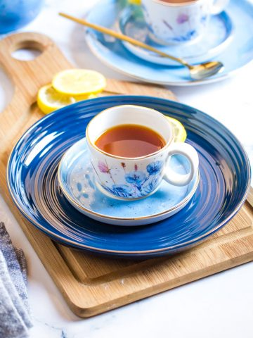 Honey Lemon Tea served in small white patterned cups placed on blue plates.